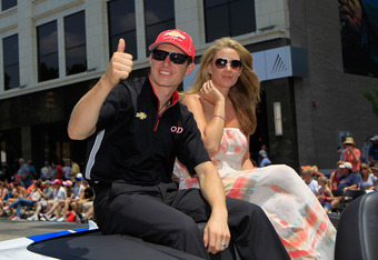 INDIANAPOLIS, IN - MAY 26:  Ryan Briscoe of Australia driver of the Team Penske Dallara Chevrolet and his wife Nicole Briscoe wave to fans during the Indianapolis 500 Festival Parade in the streets of Indianapolis on May 26, 2012 in Indianapolis, Indiana.