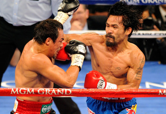 LAS VEGAS, NV - NOVEMBER 12:  Manny Pacquiao (R) throws a right at Juan Manuel Marquez during the fourth round of their WBO world welterweight title fight at the MGM Grand Garden Arena November 12, 2011 in Las Vegas, Nevada. Pacquiao retained his title wi