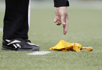 FOXBORO, MA - DECEMBER 24: A referee reaches down to pick up a penalty flag during the second half of New England's 27-24 win over the Miami Dolphins at Gillette Stadium on December 24, 2011 in Foxboro, Massachusetts.  (Photo by Winslow Townson/Getty Imag