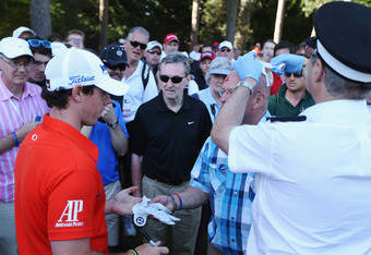 VIRGINIA WATER, ENGLAND - MAY 25:  Rory McIlroy of Northern Ireland signs his glove for a fan who was hit by an errant McIlroy shot during the second round of the BMW PGA Championship on the West Course at Wentworth on May 25, 2012 in Virginia Water, Engl