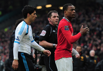 MANCHESTER, ENGLAND - FEBRUARY 11:  Patrice Evra of Manchester United celebrates victory as he walks off with Luis Suarez of Liverpool during the Barclays Premier League match between Manchester United and Liverpool at Old Trafford on February 11, 2012 in