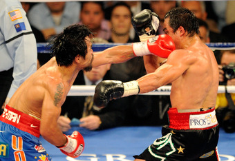 LAS VEGAS, NV - NOVEMBER 12:  (L-R) Manny Pacquiao throws a left to the face of Juan Manuel Marquez during the WBO world welterweight title fight at the MGM Grand Garden Arena on November 12, 2011 in Las Vegas, Nevada.  (Photo by Ethan Miller/Getty Images
