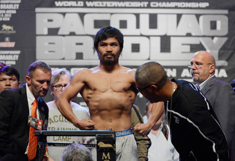 LAS VEGAS, NV - JUNE 08:  Boxer Manny Pacquiao (C) steps on the scale as Joel Diaz, Timothy Bradley's trainer, looks on during the official weigh-in for their bout at the MGM Grand Garden Arena on June 8, 2012 in Las Vegas, Nevada. Pacquiao will defend hi