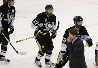 PITTSBURGH - JUNE 09:  Head coach Mike Babcock of the Detroit Red Wings walks off the ice past Evgeni Malkin #71, Petr Sykora #17, Bill Guerin #13 and Chris Kunitz #14 of the Pittsburgh Penguins as they celebrate winning Game Six of the NHL Stanley Cup Fi