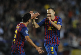BARCELONA, SPAIN - OCTOBER 19:  Andres Iniesta of FC Barcelona (R) celebrates with his teammate Xavi Hernandez after scoring the opening goal during the UEFA Champions League Group H match between FC Barcelona and FC Viktoria Plzen at Camp Nou on October