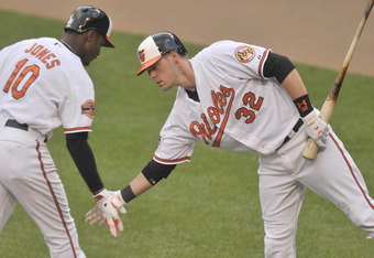 BALTIMORE, MD - MAY 10:  Adam Jones #10 of the Baltimore Orioles celebrates his home run with Matt Wieters #32 during the seventh inning of a baseball game against the Texas Rangers at Oriole Park at Camden Yards on May 10, 2012 in Baltimore, Maryland.  (