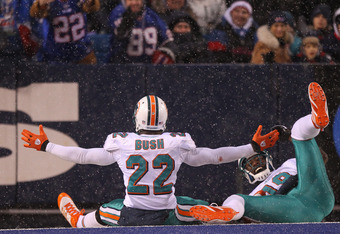 ORCHARD PARK, NY - DECEMBER 18: Reggie Bush #22 of the Miami Dolphins celebrates his touchdown with Brandon Marshall #19 during their NFL game against the Buffalo Bills at Ralph Wilson Stadium on December 18, 2011 in Orchard Park, New York. (Photo by Tom