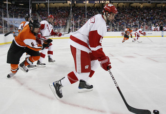 DETROIT - APRIL 08:  Justin Schultz #6 of the Wisconsin Badgers tries to keep the puck from Dan Ringwald #6 of the RIT Tigers on April 8, 2010 during the semifinals of the 2010 NCAA Frozen Four at Ford Field in Detroit, Michigan. Wisconsin defeated RIT 8-