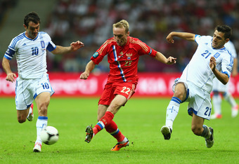 WARSAW, POLAND - JUNE 16:  Denis Glushakov of Russia passes the ball under pressure from Giorgos Karagounis and Kostas Katsouranis of Greece during the UEFA EURO 2012 group A match between Greece and Russia at The National Stadium on June 16, 2012 in Wars