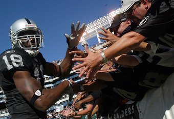 OAKLAND, CA - OCTOBER 02:  Randy Moss #18 of the Oakland Raiders celebrates with fans after the win against the Dallas Cowboys on October 2, 2005 at McAfee Coliseum in Oakland, California.  (Photo by Jonathan Ferrey/Getty Images)