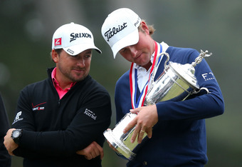 SAN FRANCISCO, CA - JUNE 17:  Webb Simpson of the United States (R) looks down at the trophy as Graeme McDowell of Northern Ireland looks on after Simpson's one-stroke victory at the 112th U.S. Open at The Olympic Club on June 16, 2012 in San Francisco, C