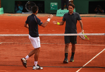 Novak Djokovic and Roger Federer, Nadal's two main challengers, shake hands after their 2012 French Open semifinal match.