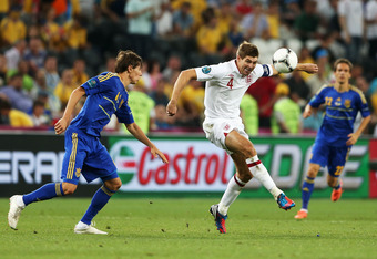 DONETSK, UKRAINE - JUNE 19:  Denys Garmash of Ukraine and Steven Gerrard of England compete for the ball during the UEFA EURO 2012 group D match between England and Ukraine at Donbass Arena on June 19, 2012 in Donetsk, Ukraine.  (Photo by Scott Heavey/Get
