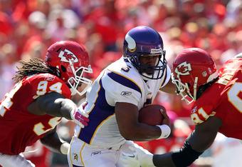 KANSAS CITY, MO - OCTOBER 02:  Quarterback Donovan McNabb #5 of the Minnesota Vikings is hit by Tyson Jackson #94 and Tamba Hali #91 of the Kansas City Chiefs as he scrambles during the game on October 2, 2011 at Arrowhead Stadium in Kansas City, Missouri