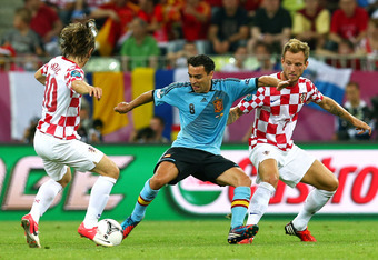 GDANSK, POLAND - JUNE 18:   Xavi of Spain is marshalled by Ivan Rakitic and Luka Modric of Croatia during the UEFA EURO 2012 group C match between Croatia and Spain at The Municipal Stadium on June 18, 2012 in Gdansk, Poland.  (Photo by Alex Grimm/Getty I