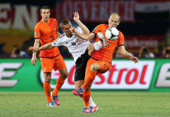KHARKOV, UKRAINE - JUNE 13:   Lukas Podolski of Germany and Arjen Robben of Netherlands battle for the ball during the UEFA EURO 2012 group B match between Netherlands and Germany at Metalist Stadium on June 13, 2012 in Kharkov, Ukraine.  (Photo by Julian