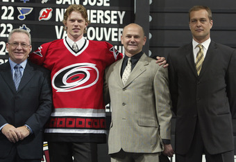 NASHVILLE, TN - JUNE 21:  Jim Rutherford, CEO and General Manager, Eric Staal, Sheldon Ferguson, Scout, and Paul Maurice of the Carolin Hurricanes pose for a portrait on stage during the 2003 NHL Entry Draft at the Gaylord Entertainment Center on June 21,