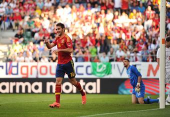 ST GALLEN, SWITZERLAND - MAY 26: Adrian Lopez (L) of Spain celebrates after scoring as goalkeeper Damir Kahriman (C) sits and Branislav Ivanovic of Serbia stands dejected during the international friendly match between Spain and Serbia on May 26, 2012 in