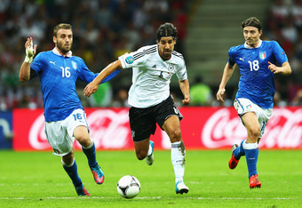 WARSAW, POLAND - JUNE 28: Daniele De Rossi (L) and Riccardo Montolivo (R) of Italy chase Sami Khedira (C) of Germany during the UEFA EURO 2012 semi final match between Germany and Italy at the National Stadium on June 28, 2012 in Warsaw, Poland.  (Photo b