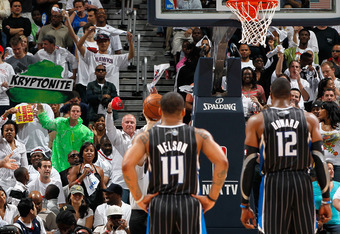 ATLANTA, GA - APRIL 24:  A fan dressed in neon green holding a green sign with the words 'Kryptonite' on it heckles Dwight Howard #12 of the Orlando Magic during a free throw against the Atlanta Hawks during Game Four of the Eastern Conference Quarterfina