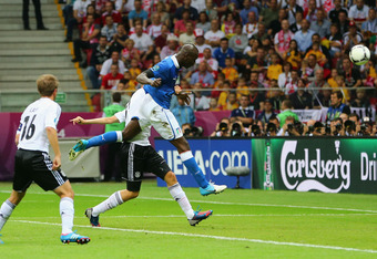 WARSAW, POLAND - JUNE 28:  Mario Balotelli (L) of Italy jumps next to Holger Badstuber of Germany to score the opening goal during the UEFA EURO 2012 semi final match between Germany and Italy at National Stadium on June 28, 2012 in Warsaw, Poland.  (Phot