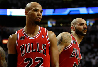 MIAMI, FL - MAY 22:  (L-R) Taj Gibson #22 and Carlos Boozer #5 of the Chicago Bulls look on against the Miami Heat in Game Three of the Eastern Conference Finals during the 2011 NBA Playoffs on May 22, 2011 at American Airlines Arena in Miami, Florida.  N