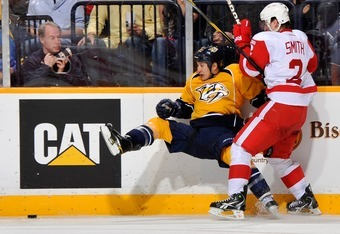 NASHVILLE, TN - MARCH 10:  Brendan Smith #2 of the Detroit Red Wings checks Jordin Tootoo #22 of the Nashville Predators at Bridgestone Arena on March 10, 2012 in Nashville, Tennessee.  (Photo by Frederick Breedon/Getty Images)