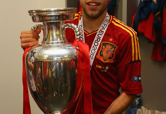 KIEV, UKRAINE - JULY 01: Jordi Alba of Spain poses with the trophy in the dressing room following the UEFA EURO 2012 final match between Spain and Italy at the Olympic Stadium on July 1, 2012 in Kiev, Ukraine.  (Photo by Handout/UEFA via Getty Images)