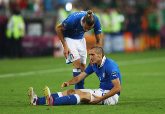 POZNAN, POLAND - JUNE 18:  Giorgio Chiellini of Italy gestures that he is injured as team mate Federico Balzaretti stands above him during the UEFA EURO 2012 group C match between Italy and Ireland at The Municipal Stadium on June 18, 2012 in Poznan, Pola