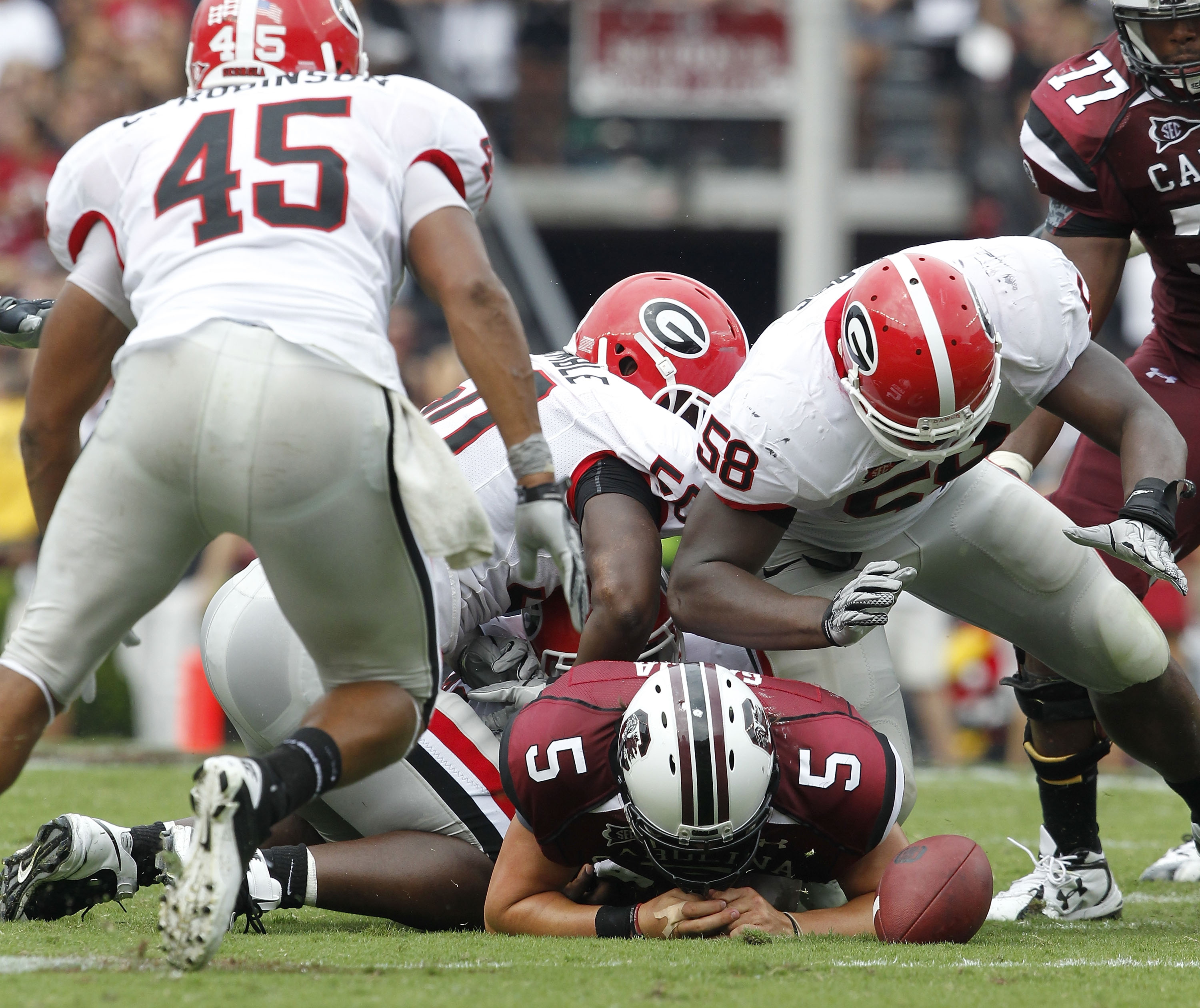 COLUMBIA, SC - SEPTEMBER 11: Quarterback Steven Garcia #5 of the South Carolina Gamecocks fumbles after being hit by defensive end Demarcus Dobbs #58 of the Georgia Bulldogs during the game at Williams-Brice Stadium on September 11, 2010 in Columbia, Sout