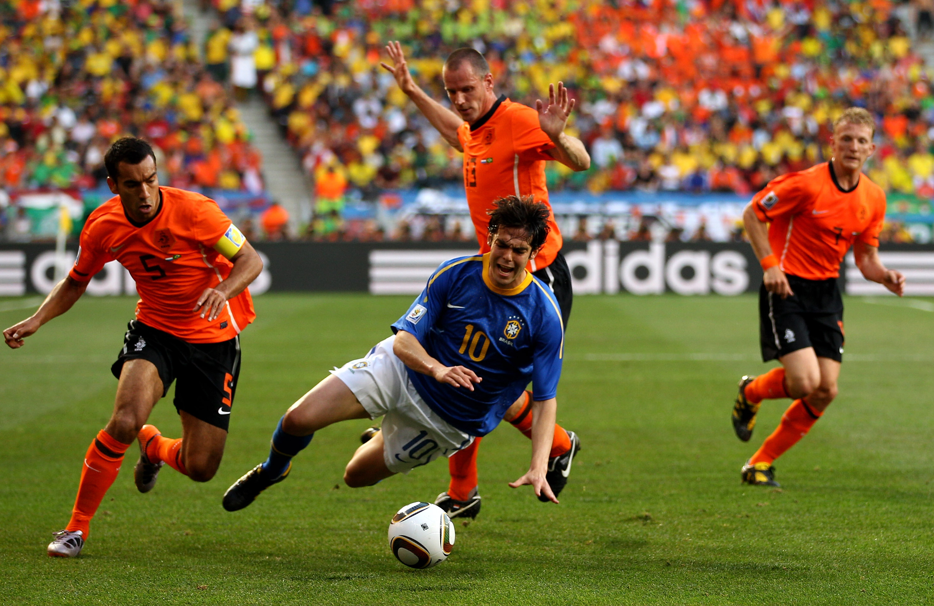PORT ELIZABETH, SOUTH AFRICA - JULY 02:  Kaka of Brazil is brought down by Giovanni Van Bronckhorst and Andre Ooijer of The Netherlands during the 2010 FIFA World Cup South Africa Quarter Final match between Netherlands and Brazil at Nelson Mandela Bay St
