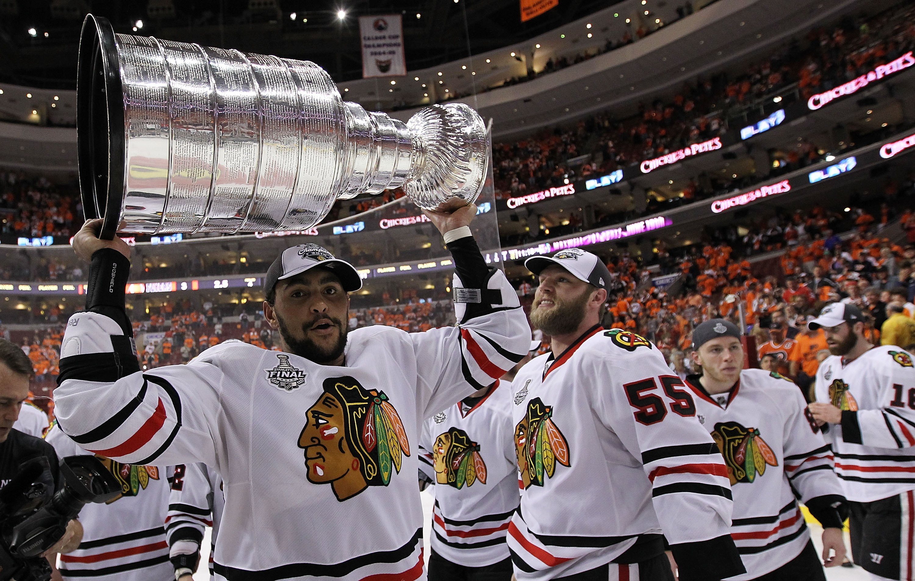Dustin Byfuglien hoists the Stanley Cup while wearing a Blackhawks jersey for the last time.