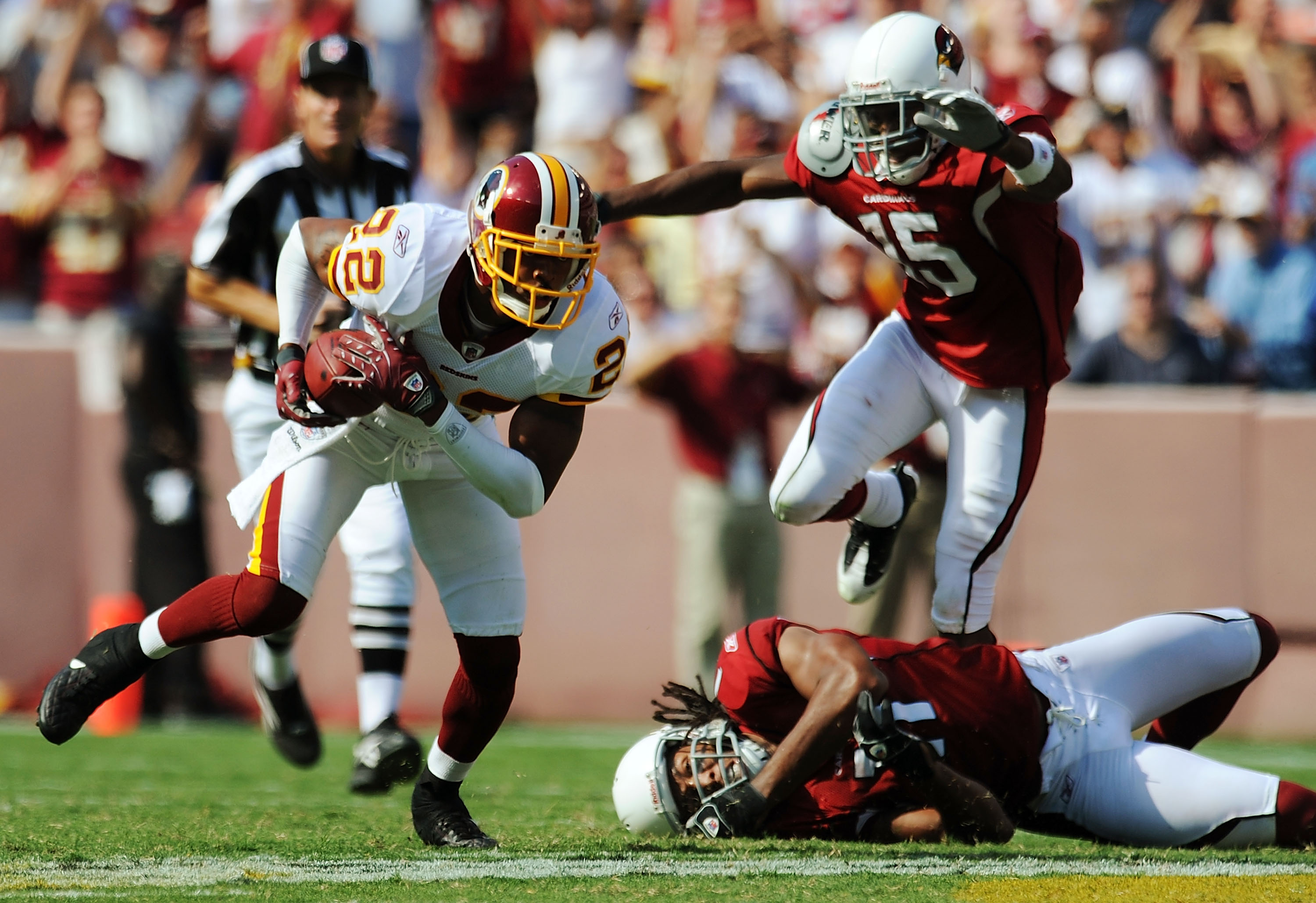 LANDOVER, MD - SEPTEMBER 21: Carlos Rogers #22 (L) of the Washington Redskins takes off on a long interception return against Arizona Cardinals Steve Breaston #15 (Top R) and Larry Fitzgerald #11 (Bottom R) at FedEx Field September 21, 2008 in Landover ,