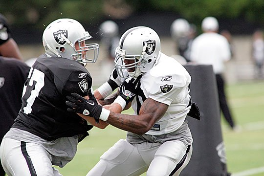 Ricky Brown gets physical with Darren McFadden.