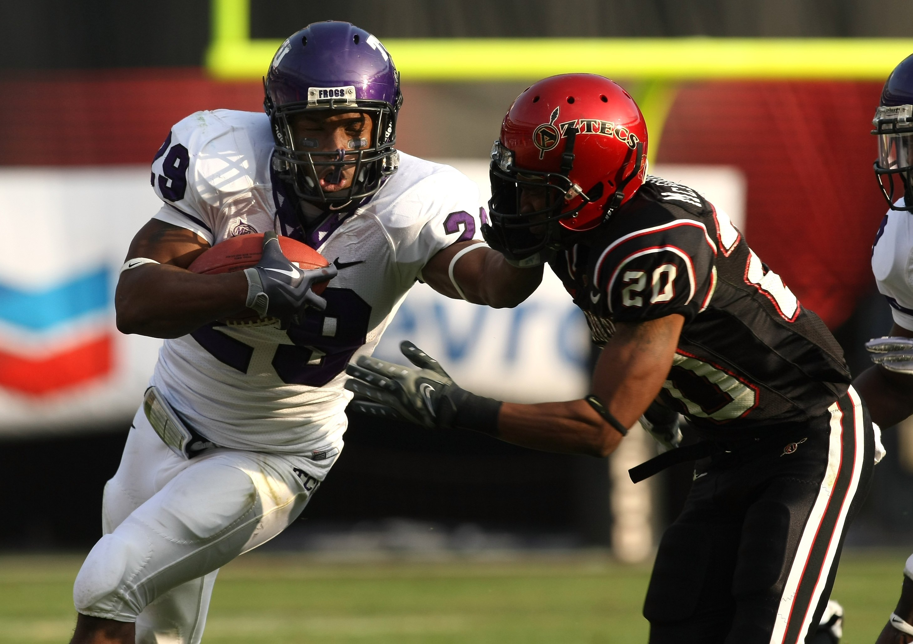 SAN DIEGO - NOVEMBER 07:  Running back Matthew Tucker #29 of the Texas Christian University Horned Frogs carries the ball as he stiffarms corner back Leon McFadden #20 of the San Diego State Aztecs on November 7, 2009 at Qualcomm Stadium in San Diego, Cal