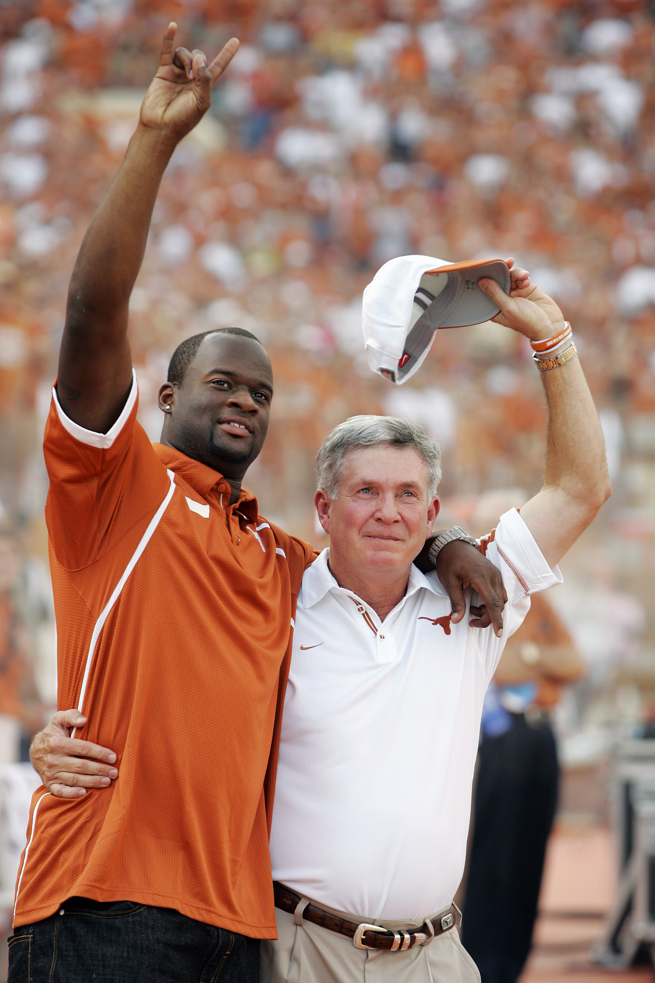 AUSTIN, TX - AUGUST 30:  Quarterback Vince Young of the Tennessee Titans and formerly with the Texas Longhorns hugs coach Mack Brown as his number is retired before a game against the Florida Atlantic Owls at Darrell K Royal-Texas Memorial Stadium on Augu