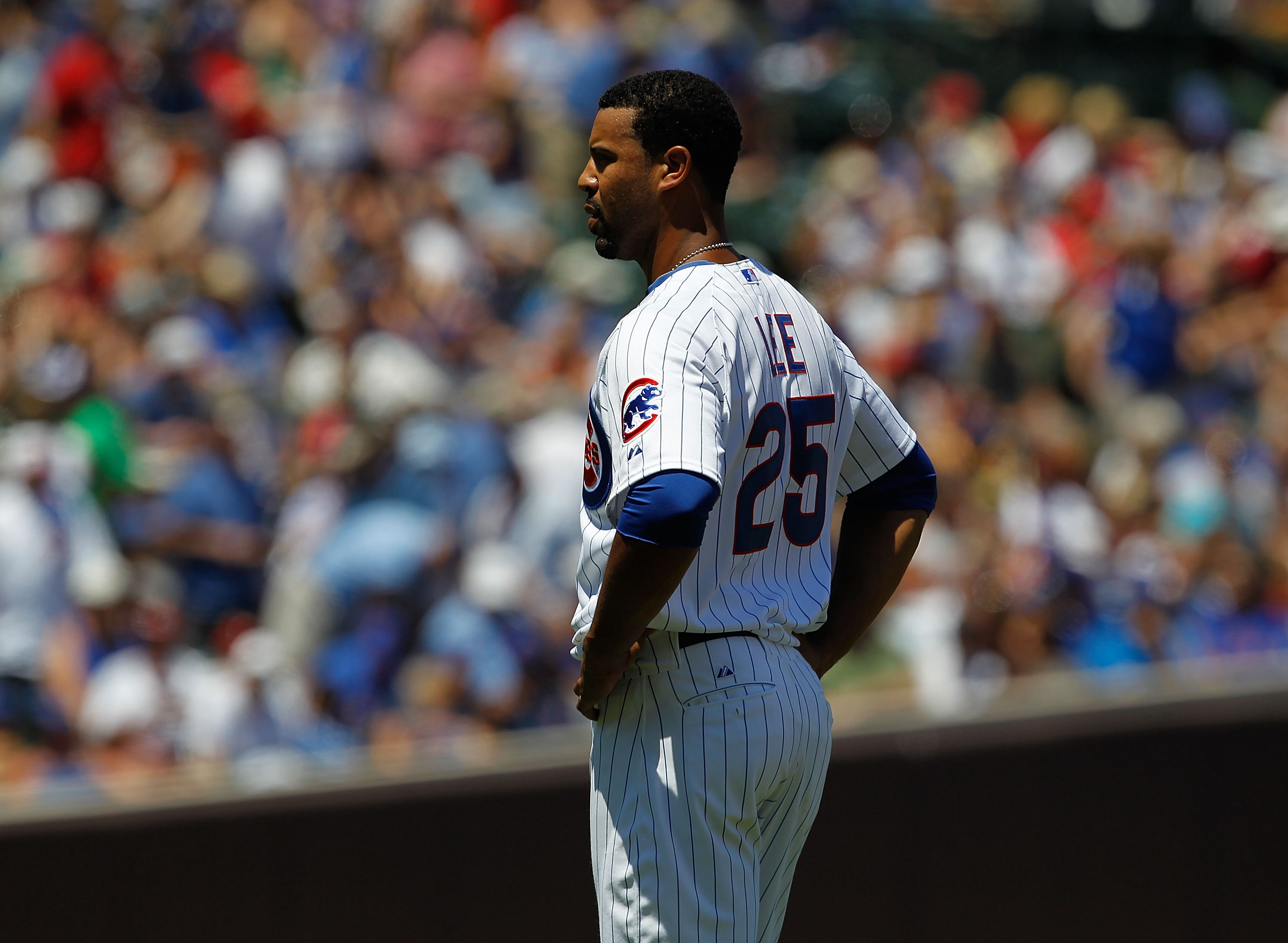 CHICAGO - JULY 03: Derrek Lee #25 of the Chicago Cubs stands and waits for a teammate to bring him his hat and glove after flying out to end an inning against the Cincinnati Reds at Wrigley Field on July 3, 2010 in Chicago, Illinois. The Cubs defeated the