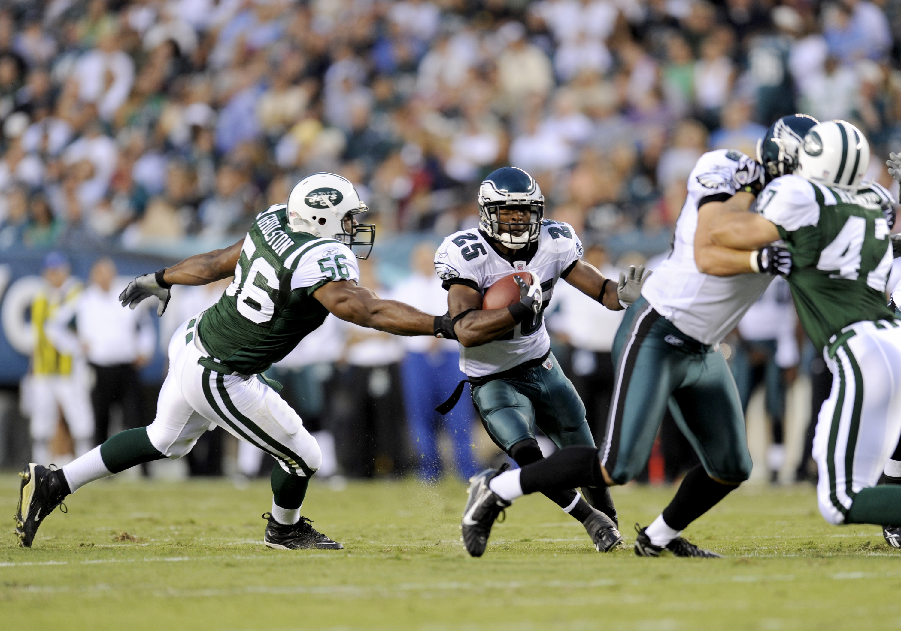 PHILADELPHIA - AUGUST 28: Lorenzo Booker #25 of the Philadelphia Eagles rushes as Vernon Gholston #56 of the New York Jets tries to make a tackle during a preseason game at Lincoln Financial Field on August 28, 2008 in Philadelphia, Pennsylvania. (Photo b