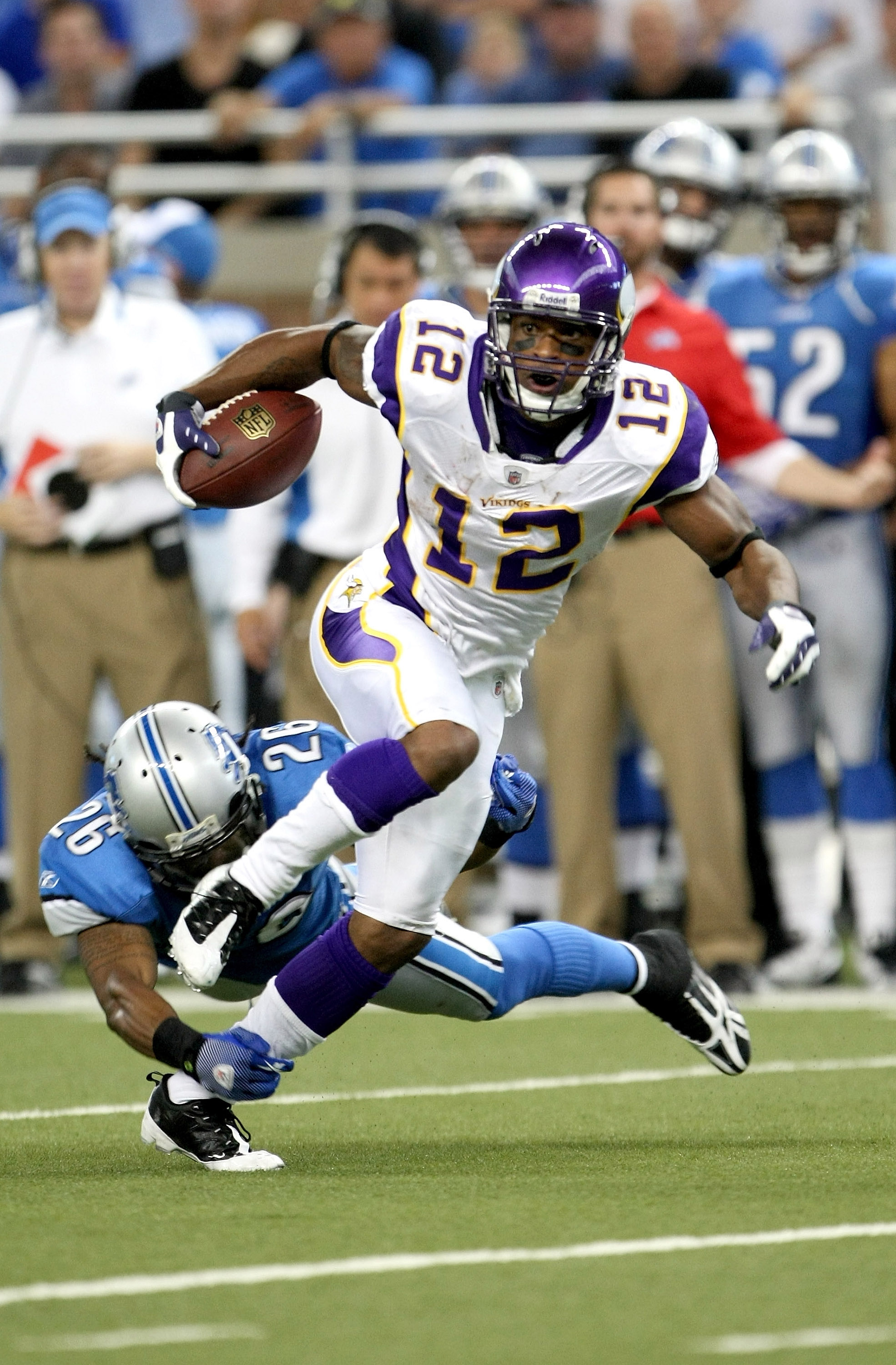DETROIT - SEPTEMBER 20:  Wide receiver Percy Harvin #12 of the Minnesota Vikings carries the ball past safety Louis Delmas #26 of the Detroit Lions at Ford Field on September 20, 2009 in Detroit, Michigan. The Vikings won 27-13.  (Photo by Stephen Dunn/Ge