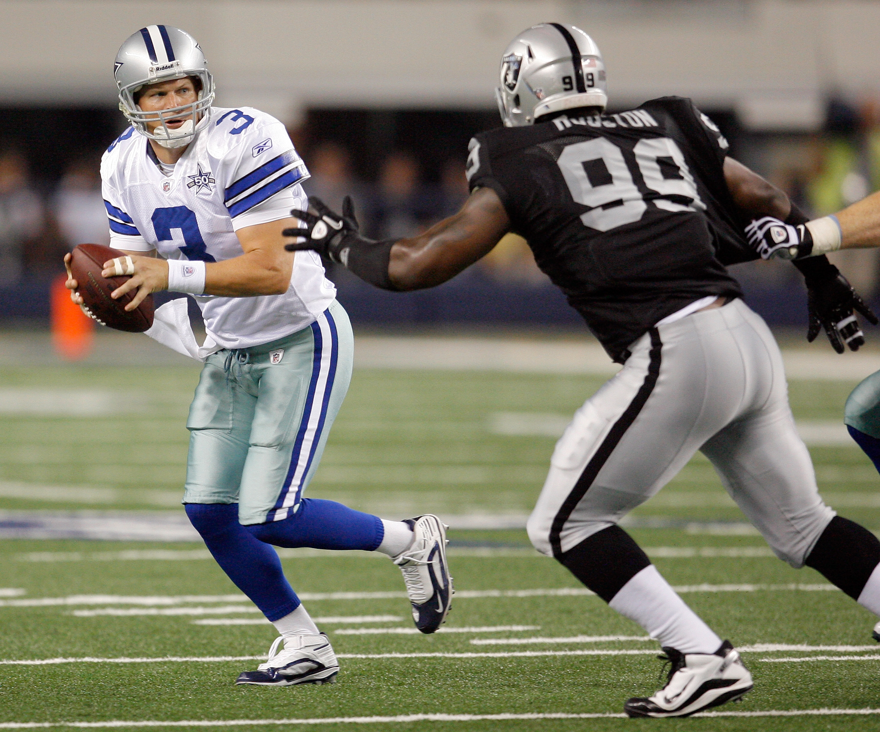 ARLINGTON, TX - AUGUST 12: Jon Kitna #3 of the Dallas Cowboys looks to pass against Lamarr Houston #99 of the Oakland Raiders during the preseason game at the Dallas Cowboys Stadium on August 12, 2010 in Arlington, Texas. (Photo by Tom Pennington/Getty Im