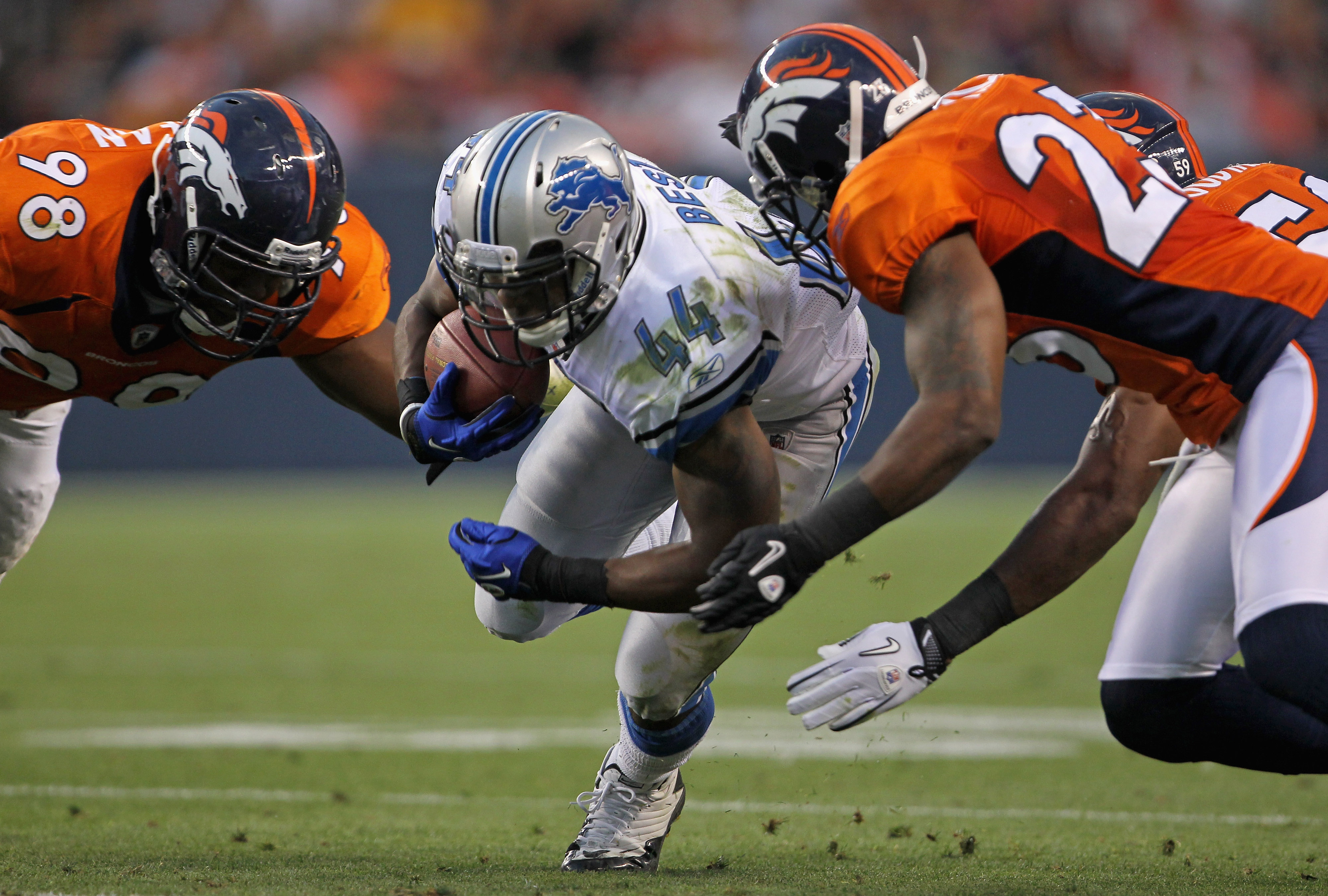 DENVER - AUGUST 21:  Jahvid Best #44 of the Detroit Lions rushes the ball as Ryan McBean #98 and Renaldo Hill #23 of the Denver Broncos make the stop during preseason NFL action at INVESCO Field at Mile High on August 21, 2010 in Denver, Colorado. The tou