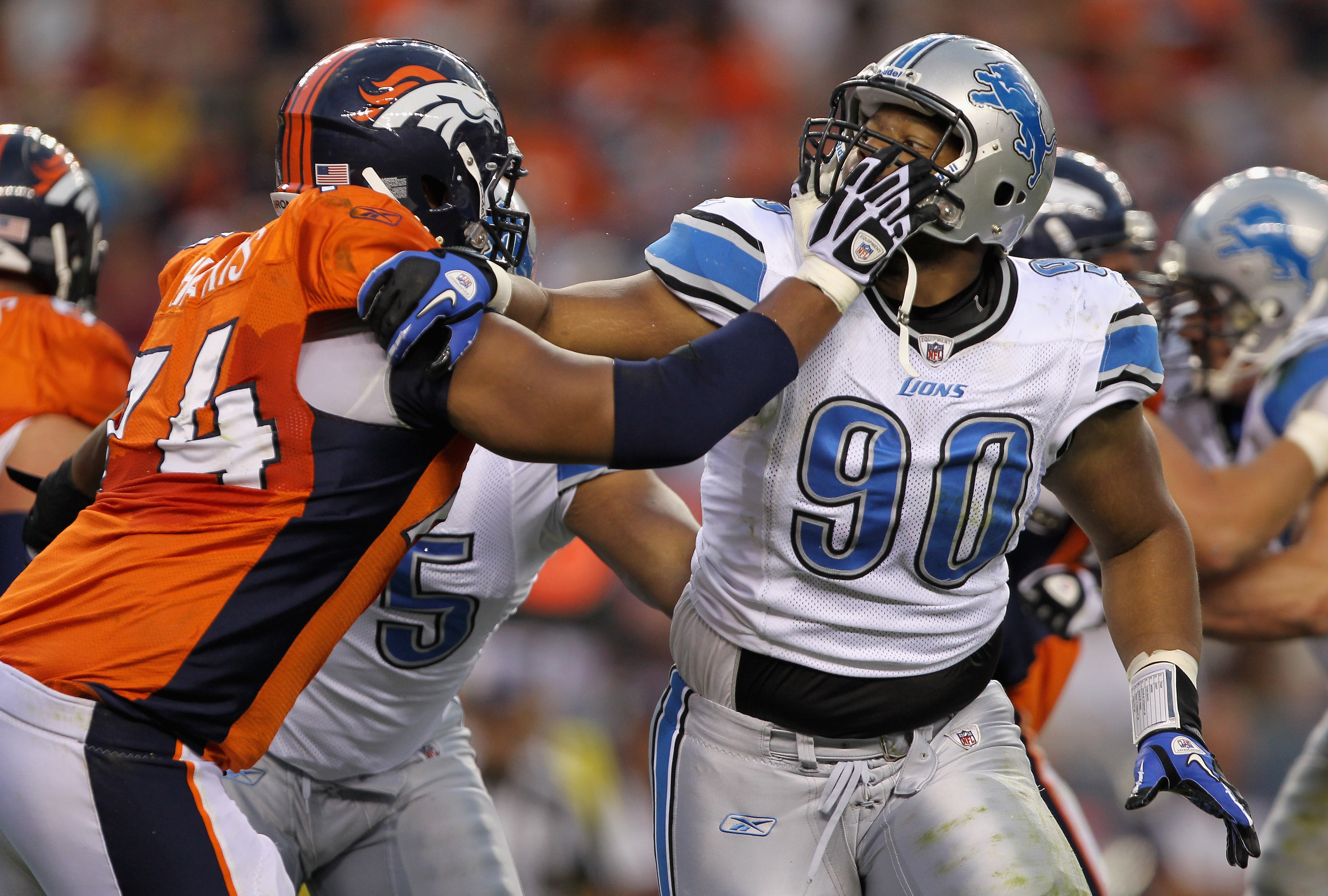 DENVER - AUGUST 21:  Defensive tackle Ndamukong Suh #90 of the Detroit Lions battles the blocking of offensive tackle Ryan Harris #74 of the Denver Broncos during preseason NFL action at INVESCO Field at Mile High on August 21, 2010 in Denver, Colorado.