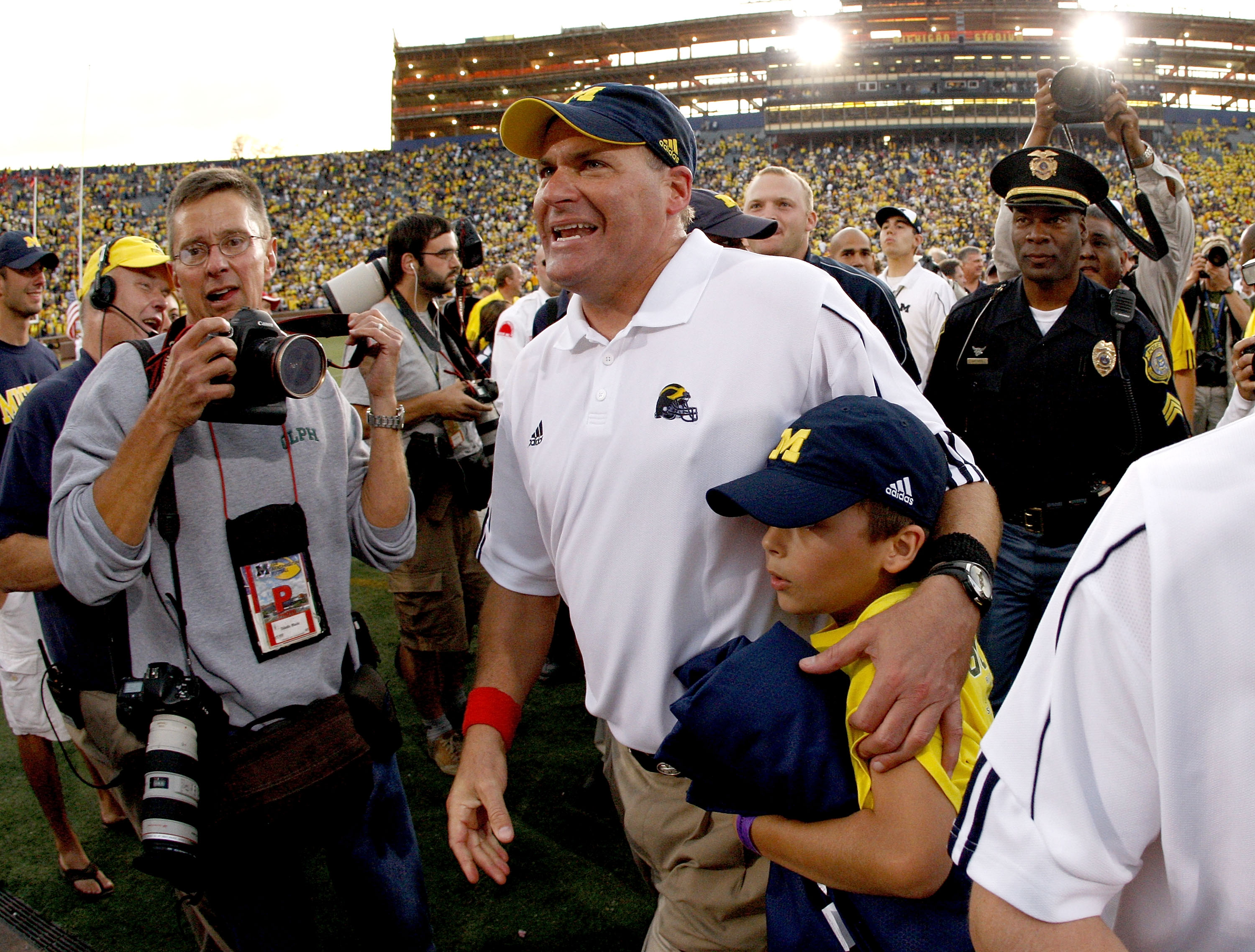 ANN ARBOR, MI - SEPTEMBER 27:  Head coach Rich Rodriguez of the Michigan Wolverines leaves the field with his son Rhett after defeating the Wisconsin Badgers on September 27, 2008 at Michigan Stadium in Ann Arbor, Michigan.  (Photo by Gregory Shamus/Getty