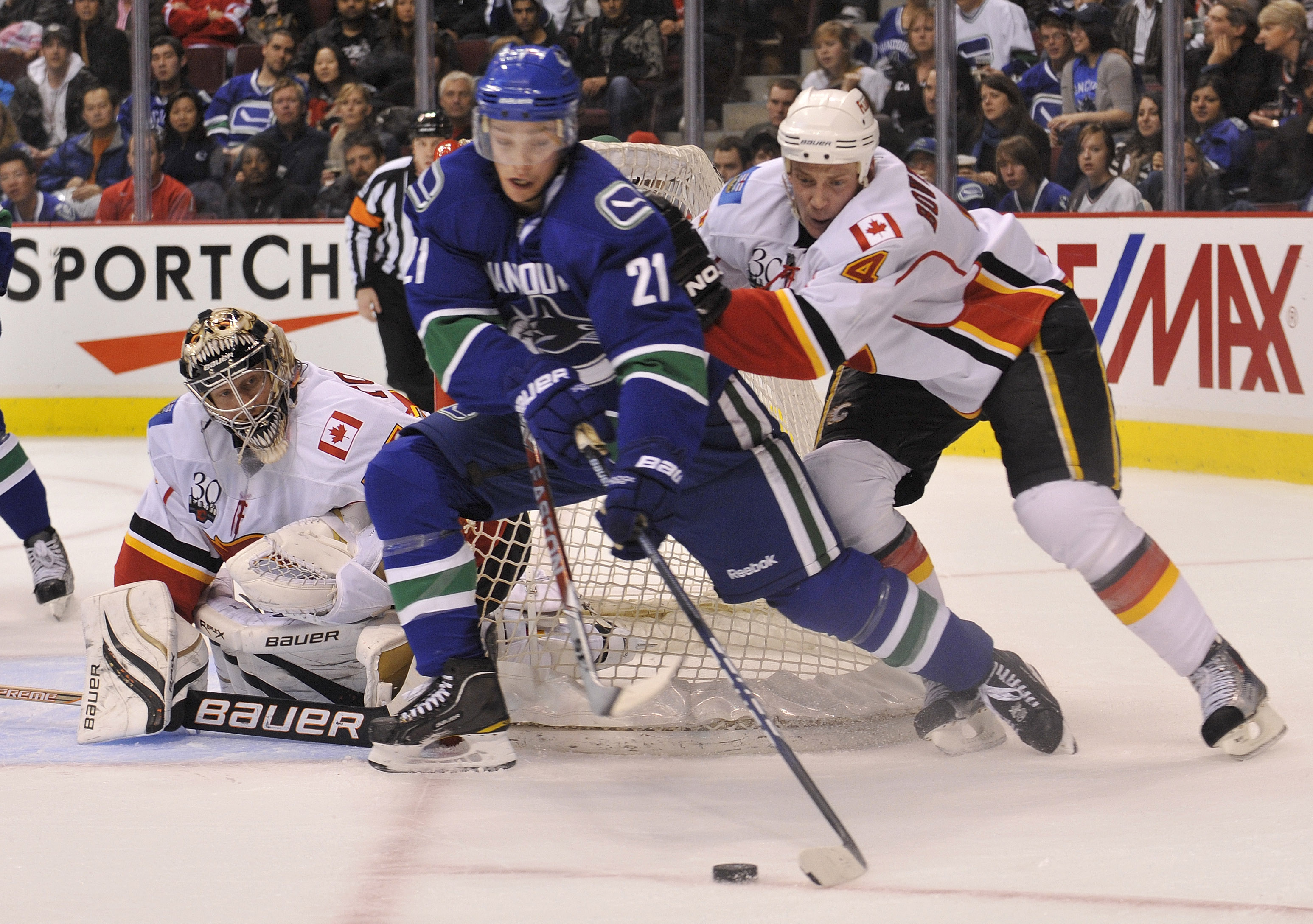 VANCOUVER, CANADA - MARCH 14: Goalie Vesa Toskala #35 of the Calgary Flames keeps an eye on Mason Raymond #21 of the Vancouver Canucks as he comes from behind the net while being checked by Flames Jay Bouwmeester #4 during the second period of NHL action