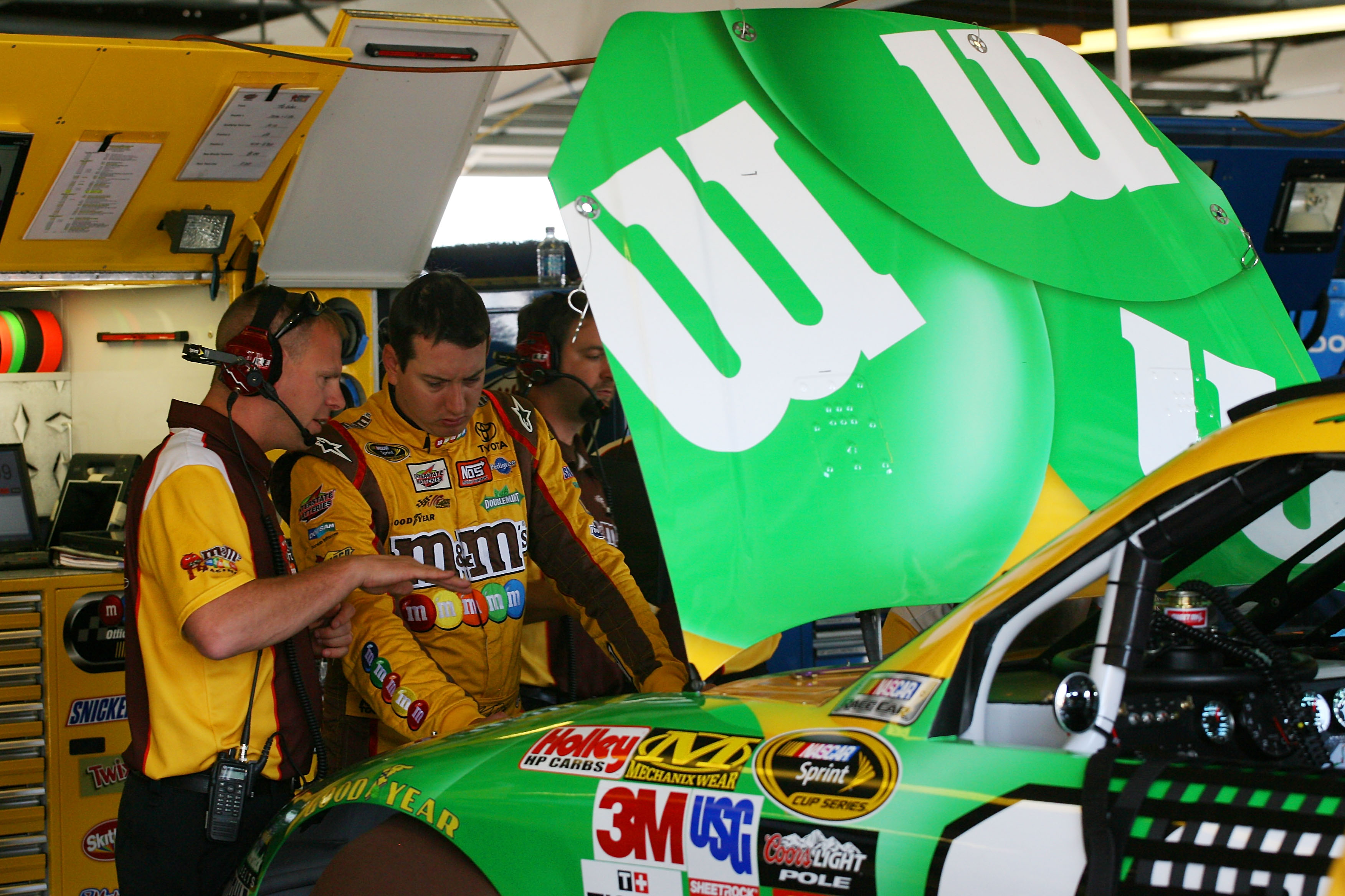 WATKINS GLEN, NY - AUGUST 06:  Kyle Busch (R), driver of the #18 M&M's Toyota, talks with his crew chief Dave Rogers in the garage during practice for the NASCAR Heluva Good! Sour Cream Dips at The Glen on August 6, 2010 in Watkins Glen, New York.  (Photo