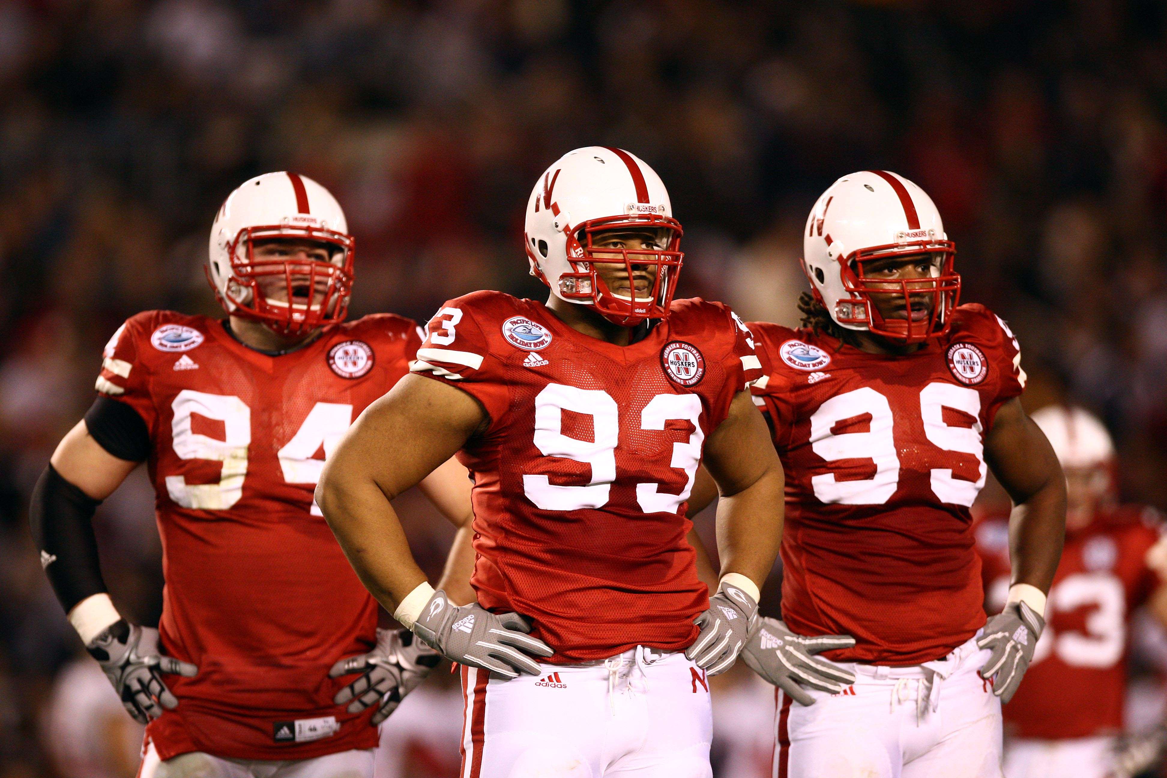 SAN DIEGO, CA - DECEMBER 30:  Defensive Tackle Ndamukong Suh #93 of the University of Nebraska Cornhuskers looks on with teammates Jared Crick #94 and Barry Turner #99 against the University of Arizona Wildcats during the Pacific Life Holiday Bowl,  on De