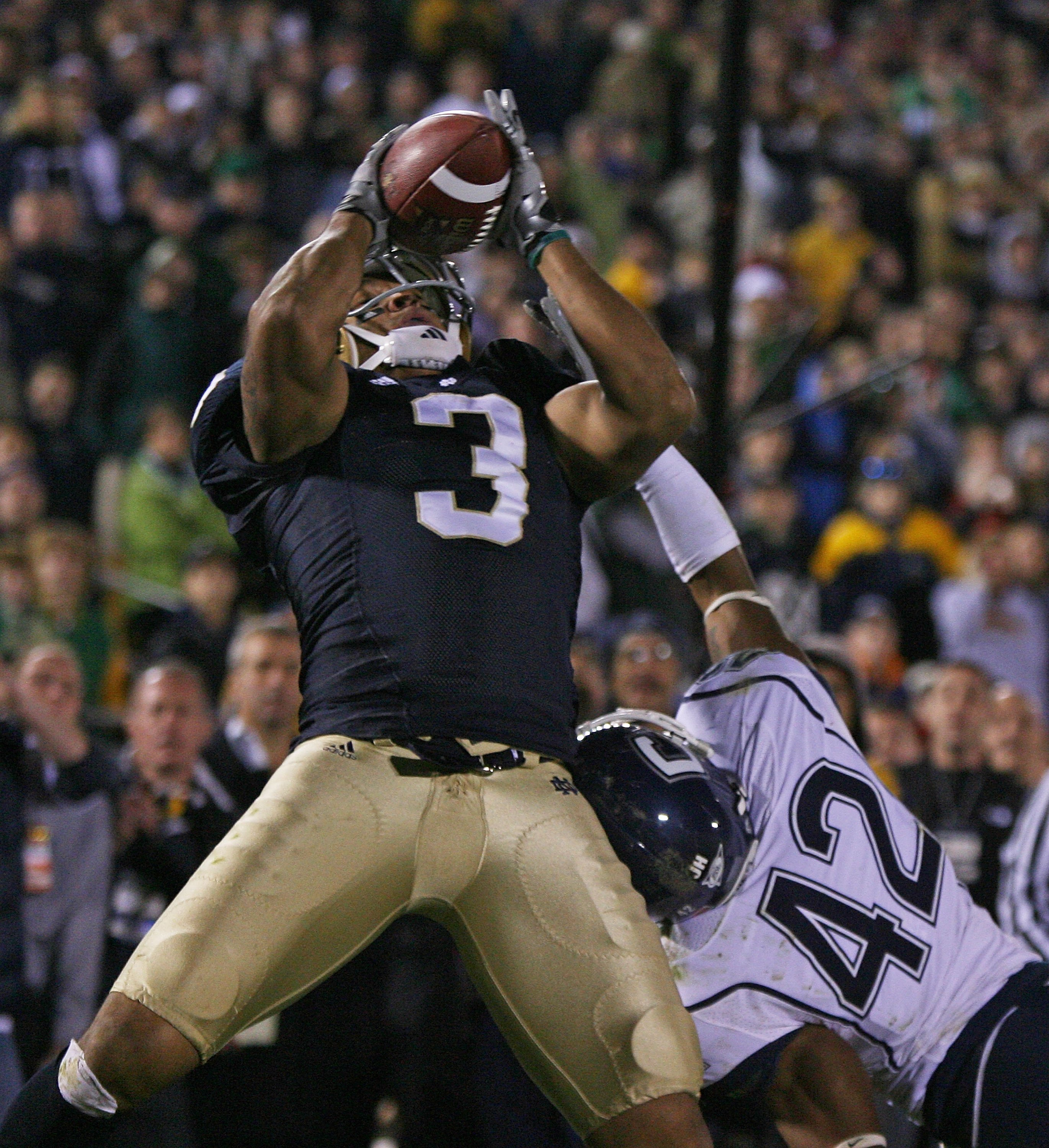 SOUTH BEND, IN - NOVEMBER 21: Michael Floyd #3 of the Notre Dame Fighting Irish catches a pass in overtime as Robert McClain #42 of the Univeristy of Connecticut Huskies defends at Notre Dame Stadium on November 21, 2009 in South Bend, Indiana. Connecticu