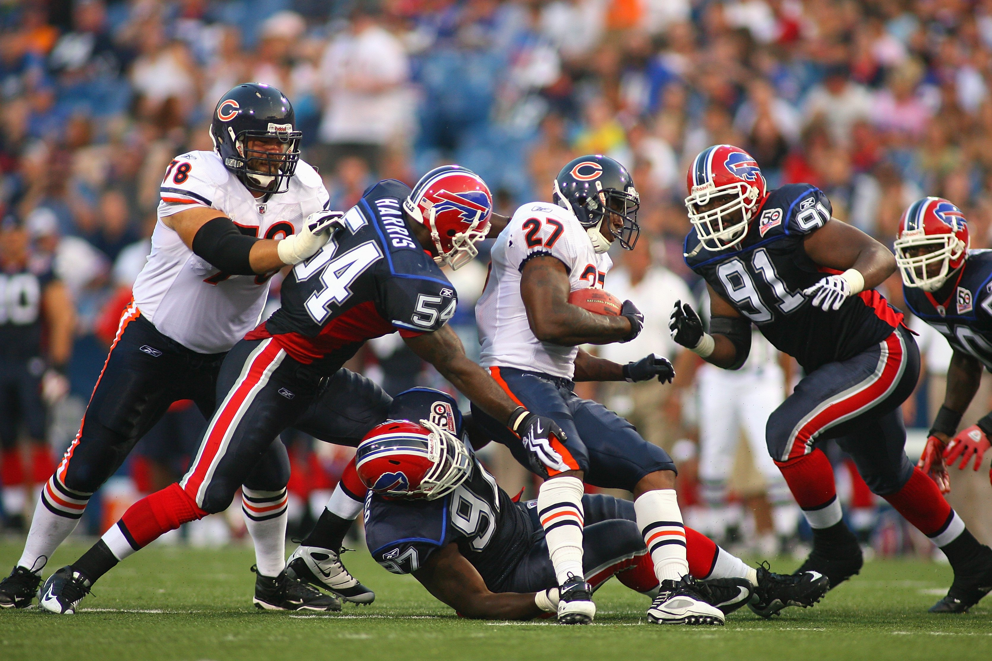 ORCHARD PARK, NY - AUGUST 15:  Running back Kevin Jones #27 of the Chicago Bears is tackled by John McCargo #97 and Nic Harris #54 of the Buffalo Bills during the preseason game on August 15, 2009 at Ralph Wilson Stadium in Orchard Park, New York. The Bil