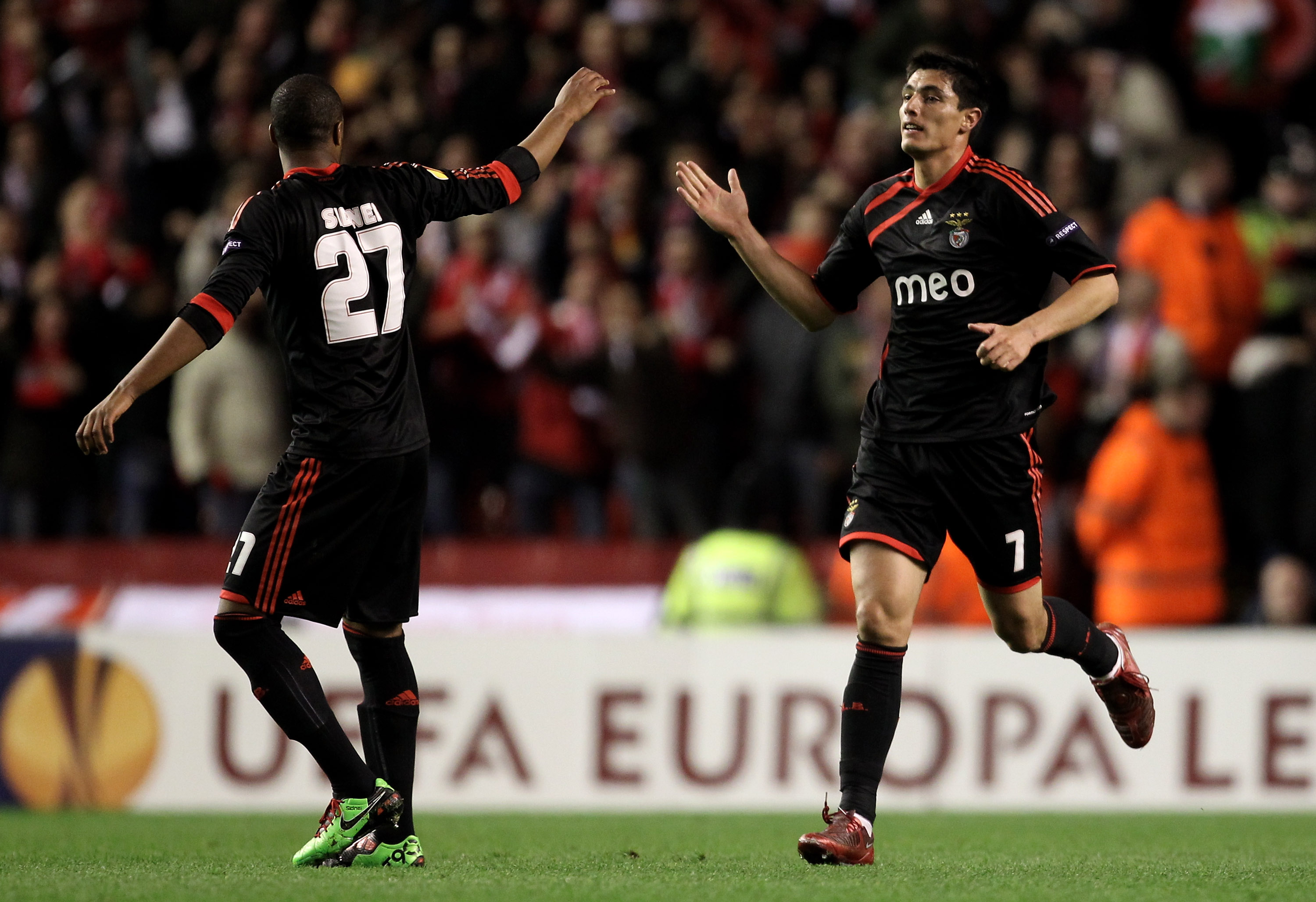 LIVERPOOL, ENGLAND - APRIL 08:  Oscar Cardozo of Benfica celebrates scoring his team's first goal with team mate Sidnei (L) during the UEFA Europa League Quarter Final second leg match between Liverpool and Benfica at Anfield on April 8, 2010 in Liverpool