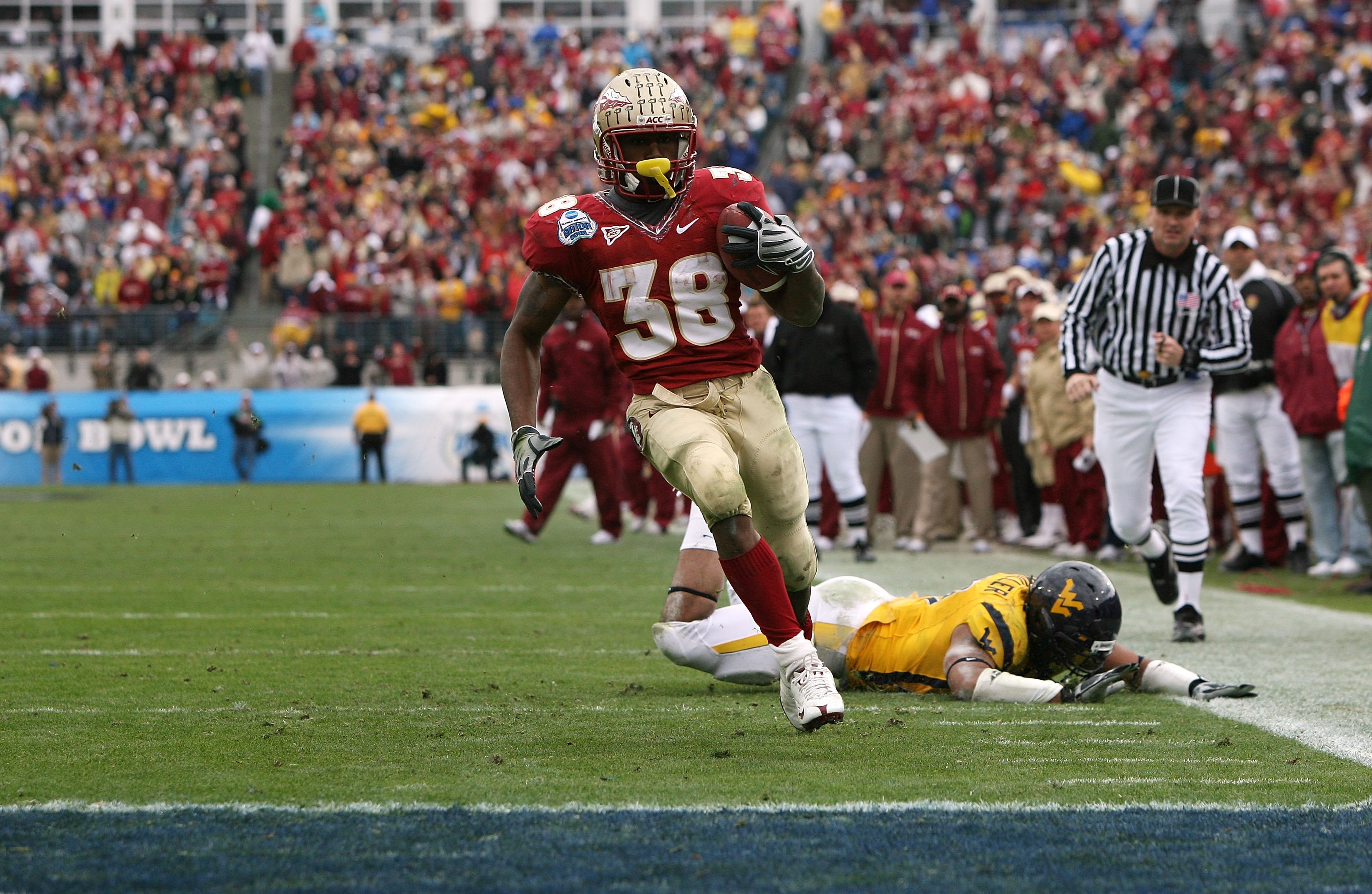 JACKSONVILLE, FL - JANUARY 01:  Running back Jermaine Thomas #38 of the Florida State Seminoles avoids a tackle attempt by linebacker Julian Miller #97 of the West Virginia Mountaineers to score a touchdown in the first quarter during the Konica Minolta G